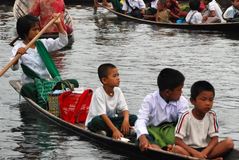 Una bambina conduce una barca all'interno di un canale piuttosto trafficato