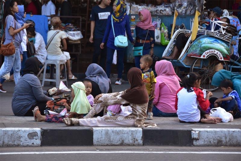 Una famiglia che si concede un pick-nik sul marciapiede divisorio di Malioboro street
